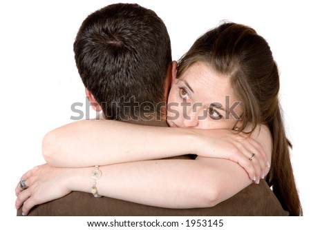 couple hugging while the woman is lokoing away in a pensive manner - stock photo