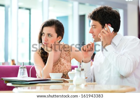 Couple in a cafe spends leisure time together, she is angry because he is busy on the phone - stock photo