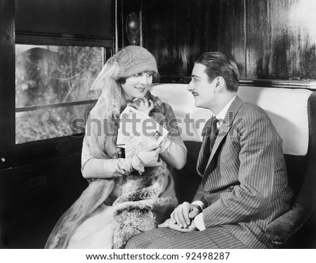 Couple in a compartment of a train looking and talking with each other - stock photo