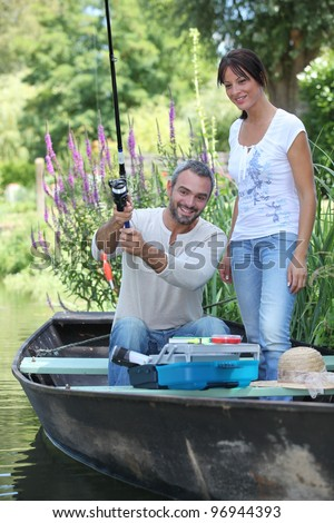 Couple in a fishing boat - stock photo