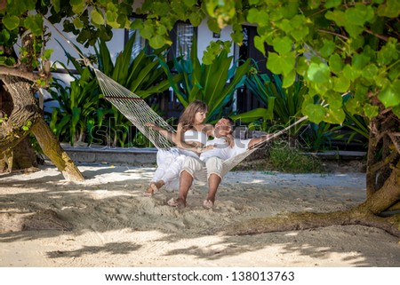 couple in a hammock on a tropical island - stock photo