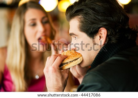 Couple in a restaurant or diner eating a hamburger and chicken wings flirting the while, shot with available light, very selective focus - stock photo