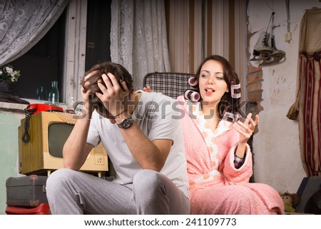 Couple in a run down retro room sitting arguing with the wife in her dressing gown gesturing and talking while the man covers his ears - stock photo