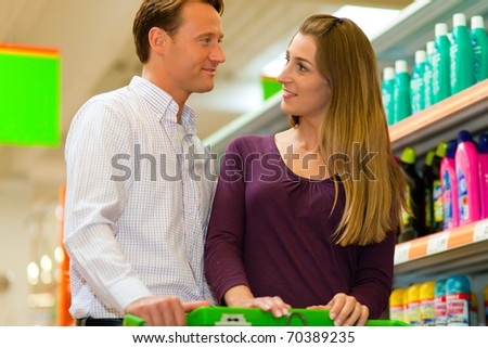 Couple in a supermarket shopping equipped with a shopping cart buying groceries and other stuff, they are looking for what they need - stock photo