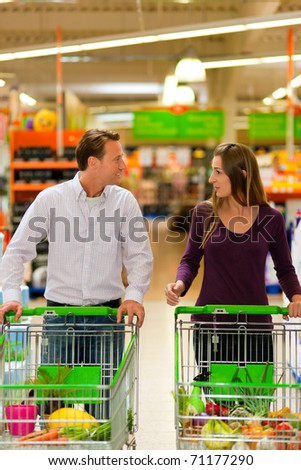 Couple in a supermarket shopping equipped with shopping carts buying groceries; they almost finished - stock photo