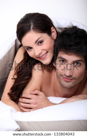 couple in bed embracing - stock photo