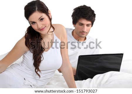 Couple in bed with a laptop - stock photo