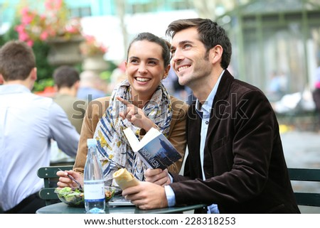 Couple in Bryant Park having lunch and reading city guide - stock photo