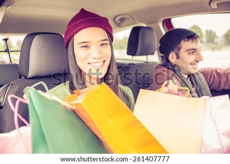 Couple in car - Candid image of two lovers in a car while driving somewhere - stock photo