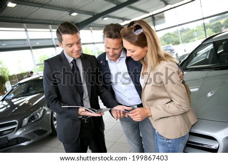 Couple in car dealership looking at brochure with salesman - stock photo