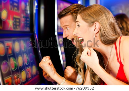 Couple in Casino on a slot machine - stock photo