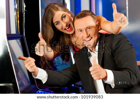 Couple in Casino on a slot machine winning and having fun - stock photo
