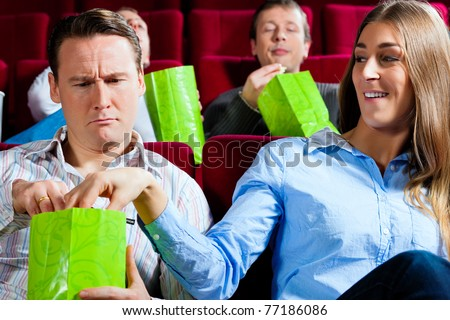 Couple in cinema watching a movie; they eating popcorn - stock photo