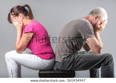 Couple in conflict sitting back to back - stock photo