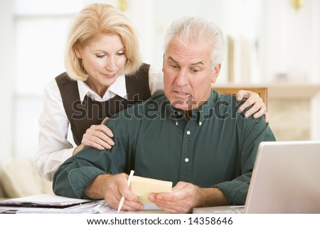 Couple in dining room with laptop and paperwork looking worried - stock photo