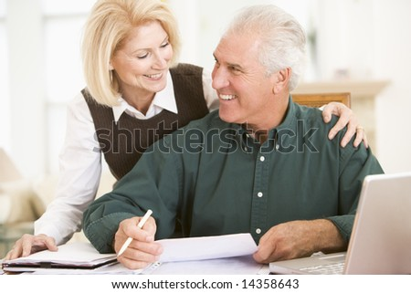 Couple in dining room with laptop and paperwork smiling - stock photo