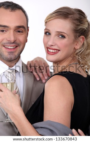 Couple in evening wear drinking champagne - stock photo