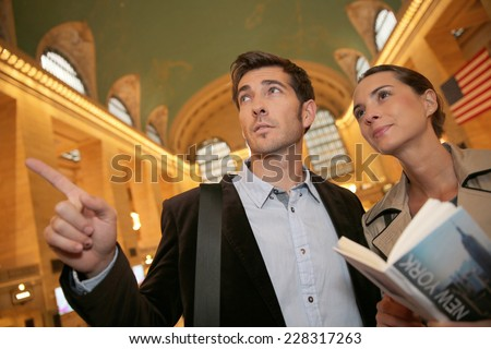 Couple in Grand Central station reading city guide - stock photo