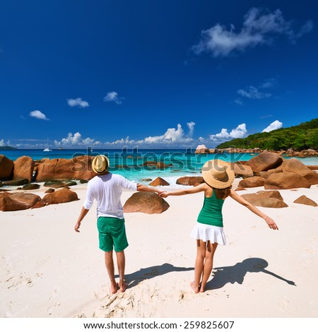 Couple in green having fun on a tropical beach at Seychelles - stock photo