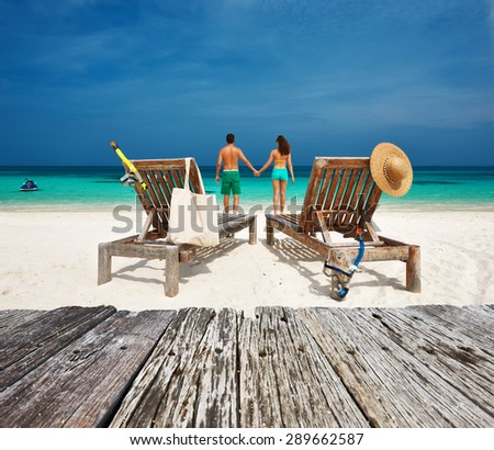 Couple in green relax on a tropical beach at Maldives - stock photo