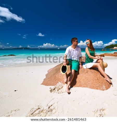 Couple in green sitting on a rock at tropical Seychelles beach - stock photo