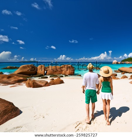 Couple in green walking on a tropical beach at Seychelles - stock photo
