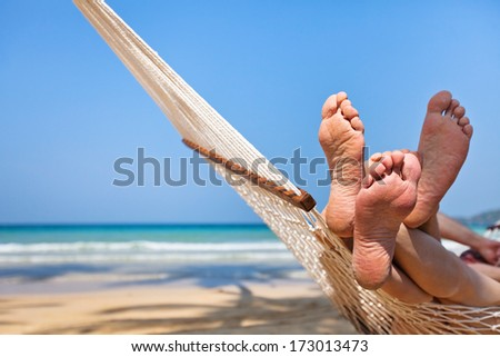 couple in hammock on the beach - stock photo