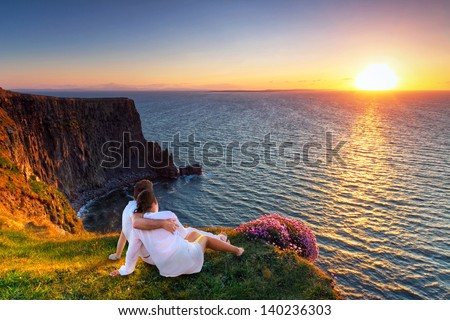 Couple in hug watching sunset on the edge of the cliff. - stock photo