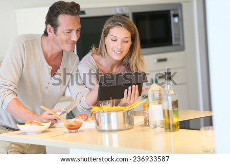 Couple in kitchen looking at pasta dish recipe on tablet - stock photo