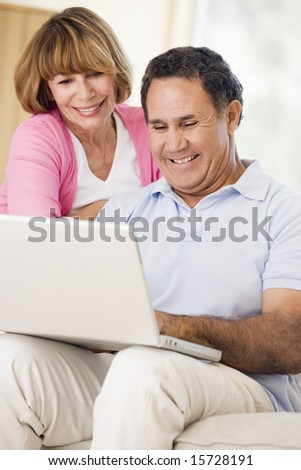Couple in living room with laptop smiling - stock photo