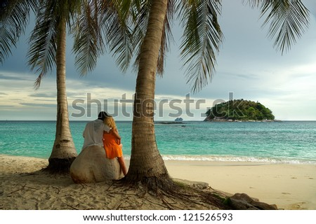 Couple in love at sunset sitting on a large rock on the beach under palm trees and looks at the island in the sea - stock photo