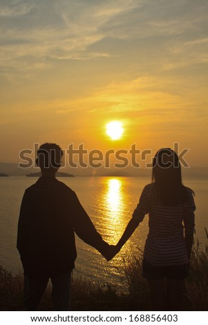 couple in love back light silhouette at lake, sunset background - stock photo