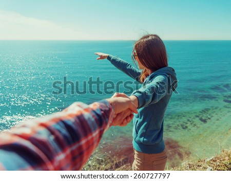 Couple in love. Beautiful young woman holding man's hand and showing him something in distance the sea. Point of view shot - stock photo