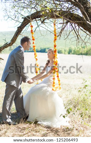couple in love bride and groom on swing in park in their wedding day - stock photo