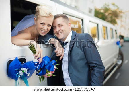 couple in love bride and groom posing at car window - stock photo