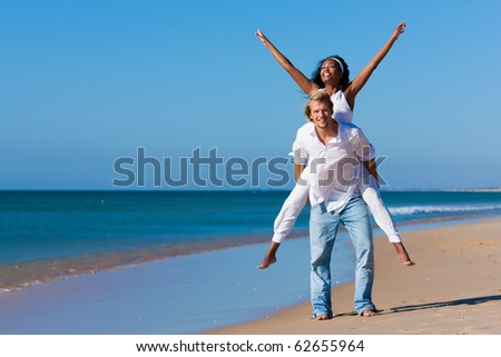 Couple in love - Caucasian man having his African-American woman piggyback on his back under a blue sky on a beach, she is stretching her arms - stock photo