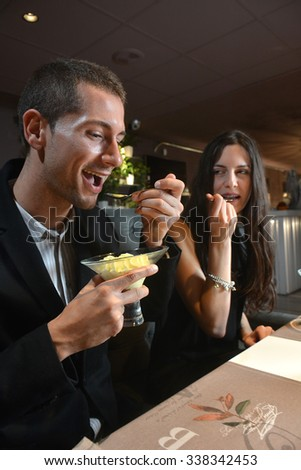 couple in love dining at an elegant restaurant and eating a tempting dessert - stock photo