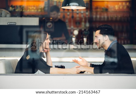 Couple in love drinking coffee laughing in coffee shop - stock photo