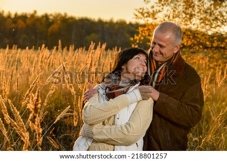 Couple in love embracing autumn sunset countryside looking each other - stock photo