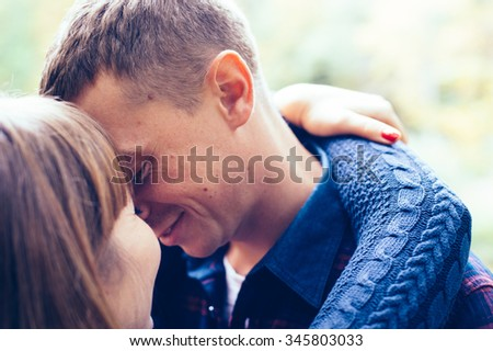 couple in love enjoy a moment of happiness in forest. handsome young man and beautiful brunette girl posing outdoor, enjoying spring holiday together. Loving couple on date in park looking happy - stock photo