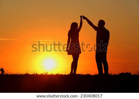 Couple in love, enjoying in nature at the sunset - stock photo