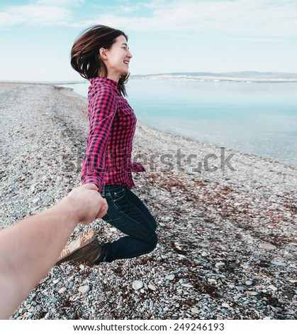 Couple in love. Happy beautiful young woman holding hand her boyfriend and jumping on beach near the sea. Point of view shot - stock photo