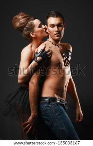 Couple in love. Happy loving couple. Biting man's ear. Dark background. - stock photo
