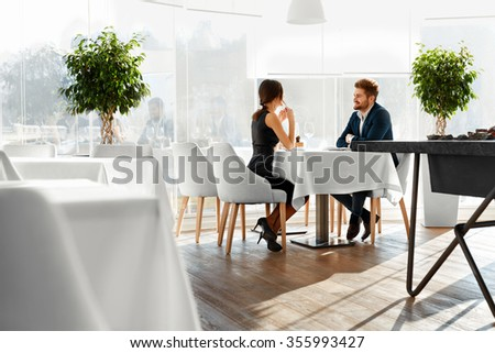 Couple In Love. Happy Smiling Elegant Young People Celebrating Anniversary Or Valentine's Day And Having Romantic Dinner Or Lunch Together In Gourmet Restaurant. Romance, Relationships Concept. - stock photo