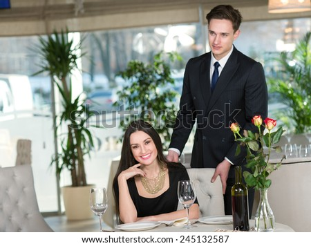 Couple in love is having romantic dinner together. Close up of beautiful girl, while her handsome man is behind her - stock photo