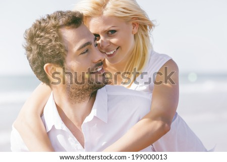 Couple in love - man having his woman piggyback on his back under a blue sky on beach - stock photo