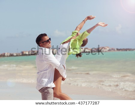 Couple in love man holding woman on hands. Two lovers in exotic vacation in idyllic nature scene sharing positive feelings and emotions. Magic moments of loving hearts.  - stock photo