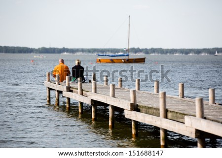 couple in love on a jetty and a sailing boat in the background - stock photo