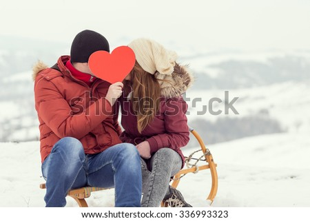 Couple in love on a winter vacation, sitting on a sleigh, hugging and kissing - stock photo