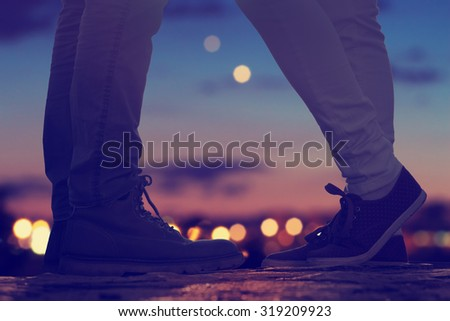 Couple in love on the street with defocused city lights and traffic. - stock photo